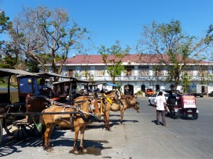 Kalesas (horse-drawn carriages) wait for tourists within the Vigan Heritage Village.